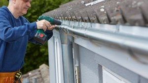 man installing a new eavestrough system